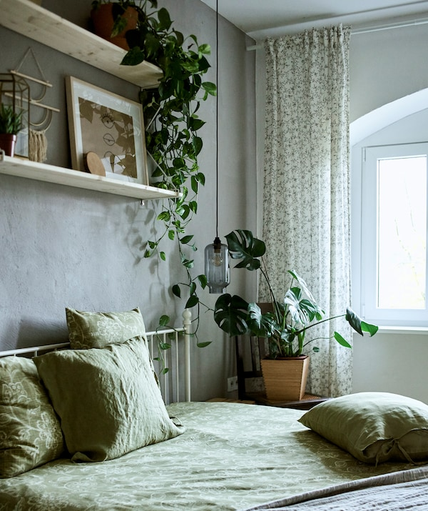 A bedroom decorated with green textiles, plants and two shelves mounted on a grey wall displaying a mix of art and trinkets.