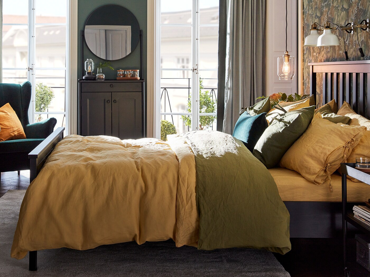 A bedroom has a bed with pillowcases and duvet covers in green and yellow, a cabinet with a mirror, and a green wing chair.