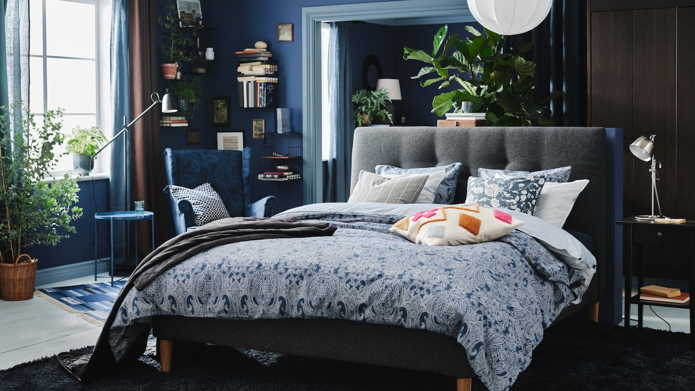 A bedroom in different shades of blue with an upholstered bed, plenty of cushions, a wing chair, books and a large rug.