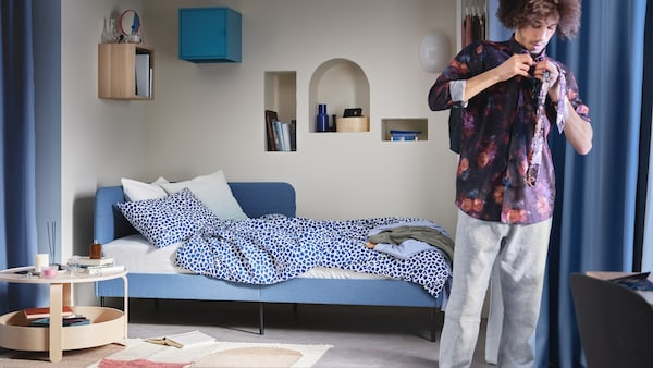 A bedroom interior with a single bed in the center of it.