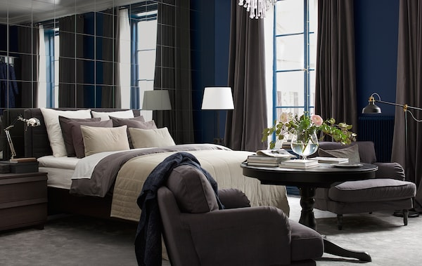 A bedroom of browns and blues has a mirror wall, a bed with lots of textiles, two armchairs, and fresh flowers.