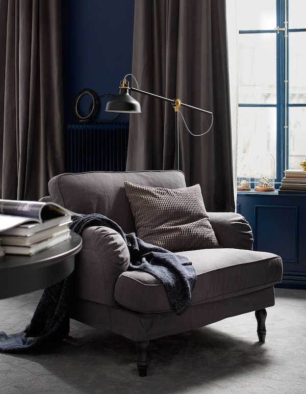 A bedroom reading area with an armchair, floor lamp, and table.