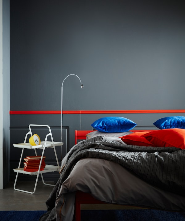A bedroom scene, with a white IKEA VIGGJA tray stand with two shelves used as a bedside table with a lamp beside it.