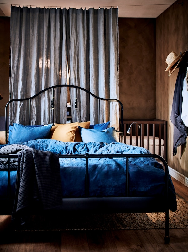 A bedroom slightly divided by two curtains with a black SAGSTUA metal bed frame in the middle of the room, and a baby cot.