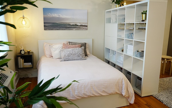 A bedroom space created using a KALLAX shelving unit gives just enough space for a white MALM twin bed and a wall mounted EKET cabinet as a side table.