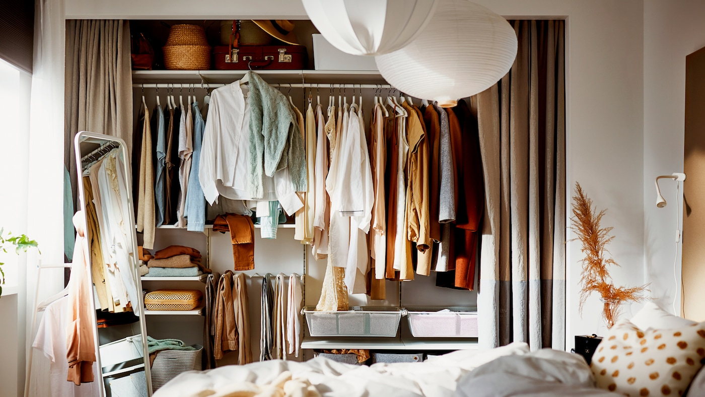 A bedroom where a wall-wide alcove has its curtains open, revealing a filled wardrobe built on a BOAXEL storage combination.
