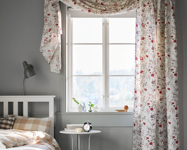A bedroom window with floral curtains.
