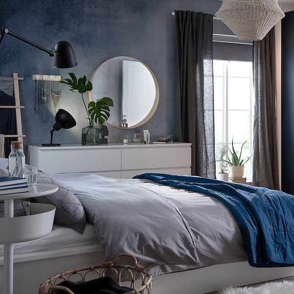 A bedroom with a bed , a mirror and different textiles