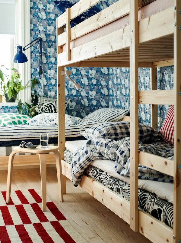 A bedroom with a bed and a bunk bed in neutral colours, a floral wallpaper and textiles in different colours and patterns.