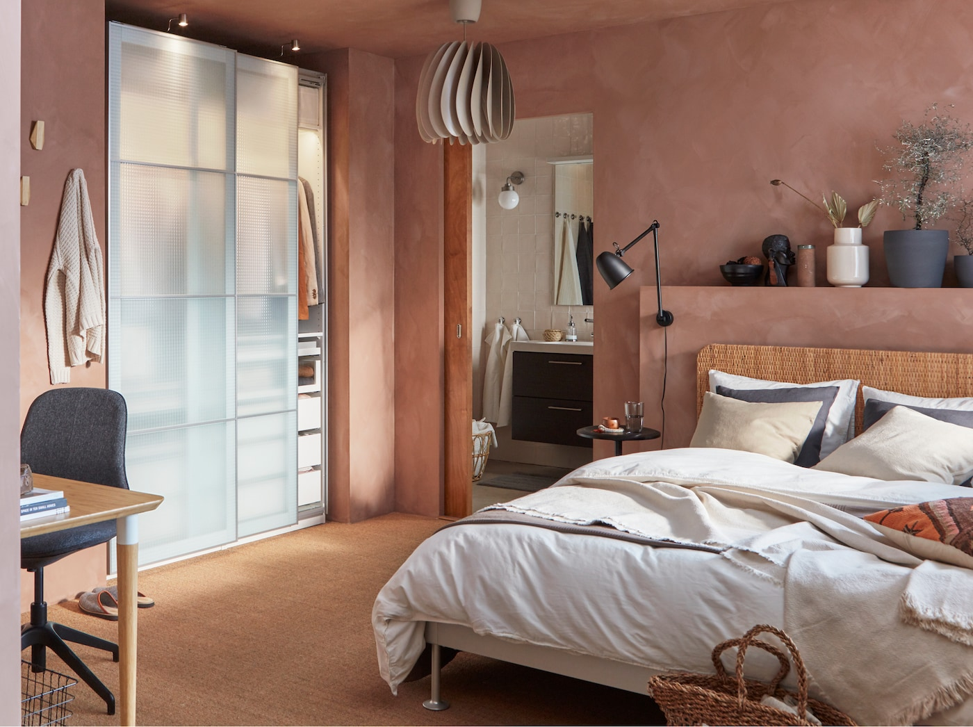 A bedroom with a bed frame in aluminium and a rattan headboard, wardrobe with frosted glass doors and a beige pendant lamp.