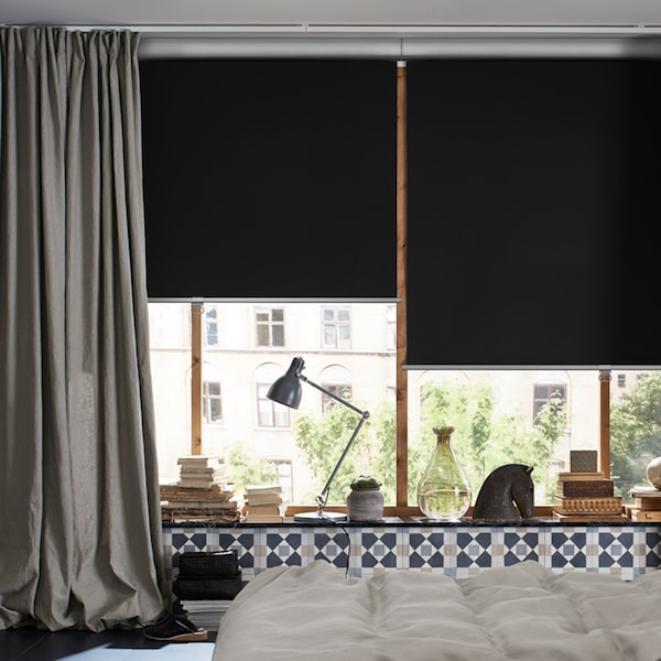 A bedroom with a bed in the middle and windows with an INGERT curtain and TRETUR block-out roller blinds pulled half-down.