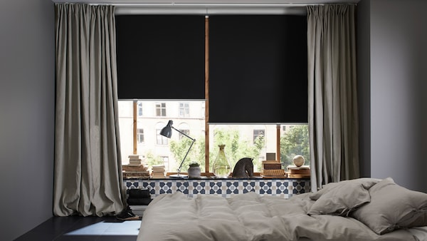 A bedroom with a bed in the middle and windows with INGERT curtains and TRETUR block-out roller blinds pulled half-down.