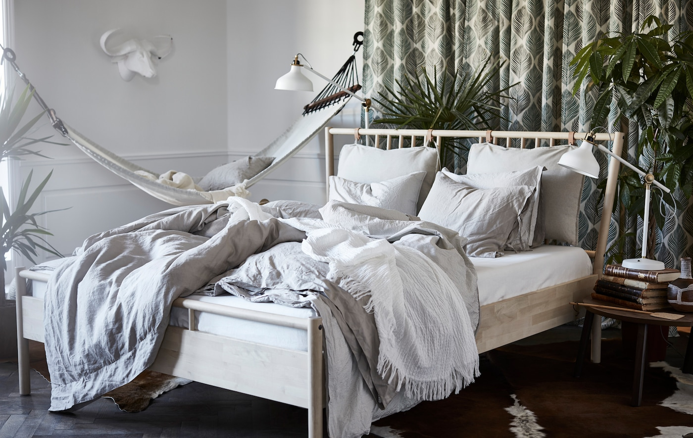 A bedroom with a BJÖRKSNÄS bed frame, RANARP lamp and STOCKHOLM coffee table.