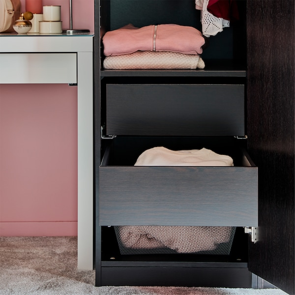 A bedroom with a black-brown wardrobe with drawers, a white dressing table, pinks walls and a grey rug.