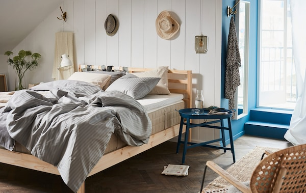 A bedroom with a blue tray table beside it