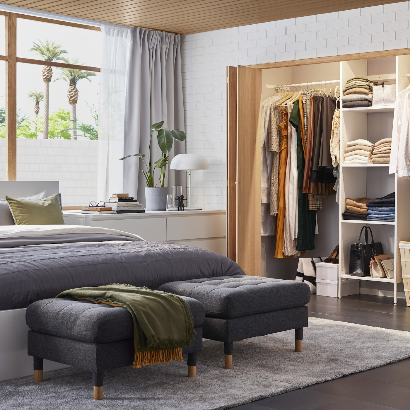 A bedroom with a built-in wardrobe solution, a white bed frame, a white chest of drawers and two dark grey footstools.