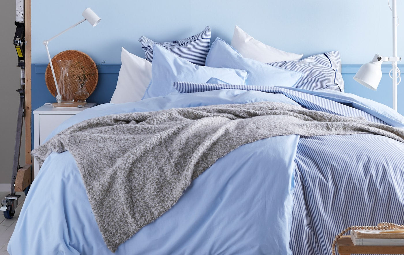 A bedroom with a color scheme of whites and light blues, with lots of blankets and pillows.