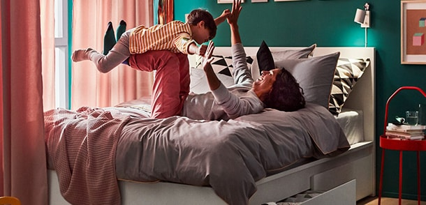 A bedroom with a dad lying on his back on a bed with his hands and feet up in the air, playing airplane with his son.