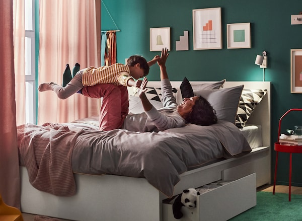 A bedroom with a dad lying on his back with hands and feet up in the air on the bed, playing airplane with his son.