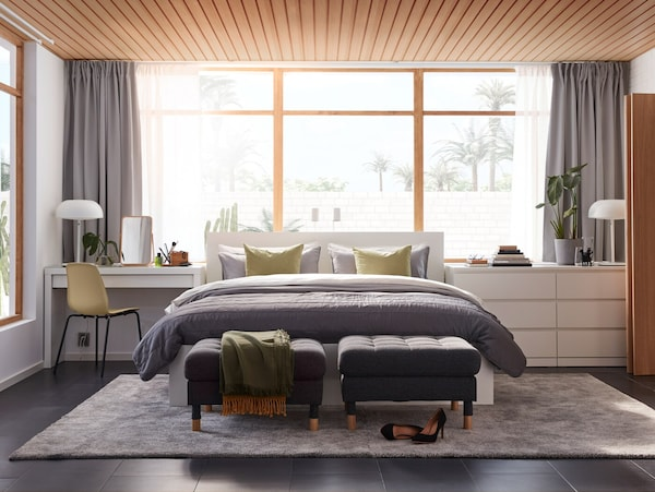 A bedroom with a dressing table, a bed frame and a chest of drawers from the MALM series and a large grey rug on the floor.