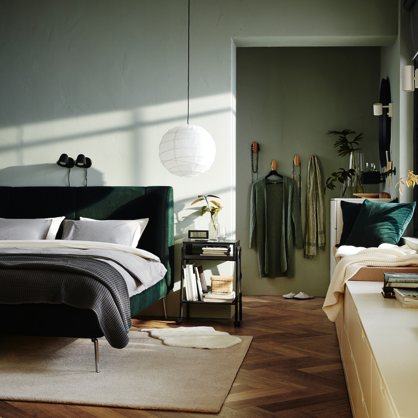A bedroom with a green upholstered bed frame, two black wall lamps, an off-white rug and a white chest of drawers.