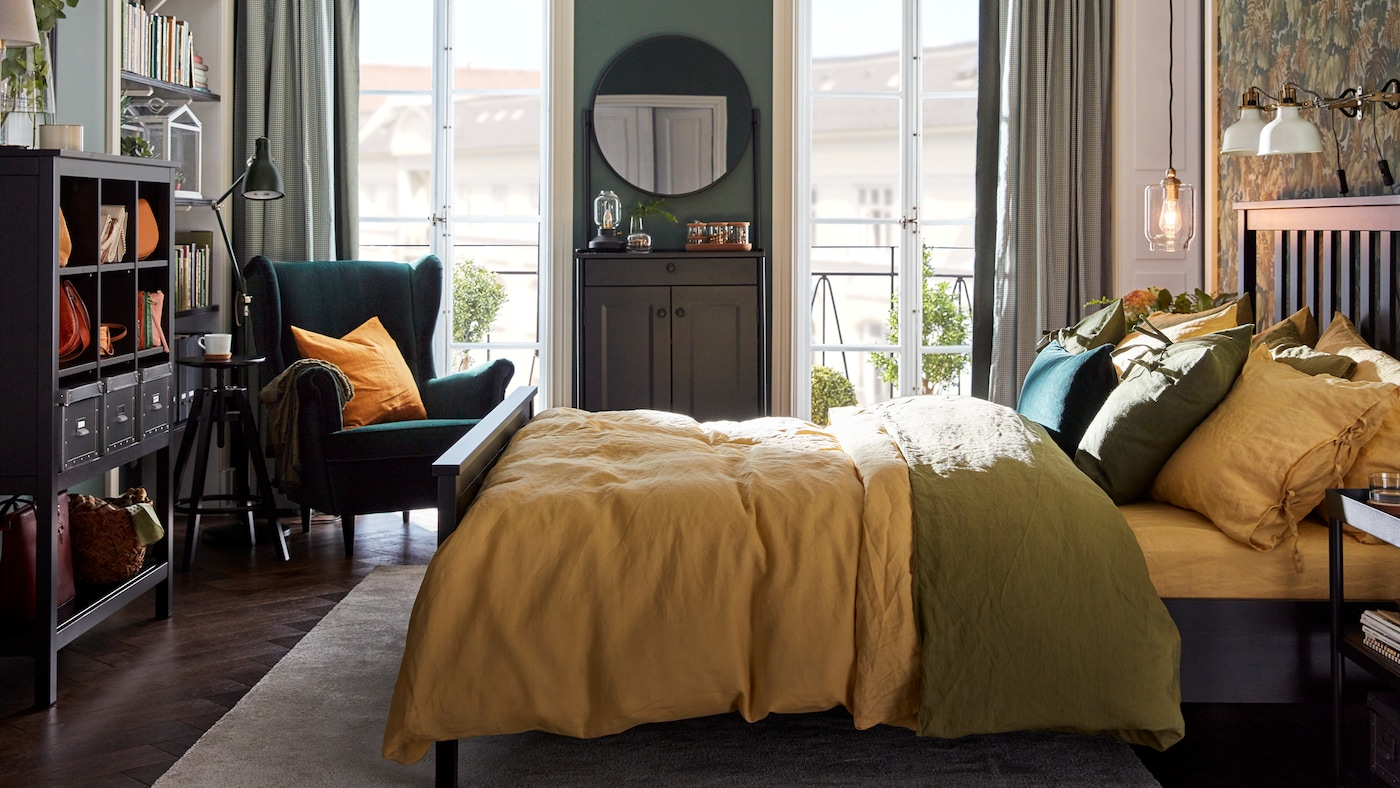 A bedroom with a HEMNES bed with colorful bed linen, a green STRANDMON chair in one corner and two balcony doors.
