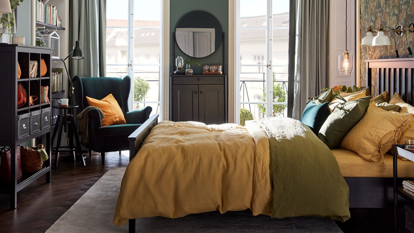A bedroom with a HEMNES bed with colourful bed linen, a green STRANDMON chair in one corner and two balcony doors.