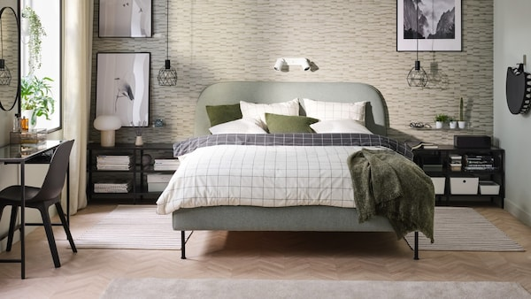 A bedroom with a light green upholstered bed.