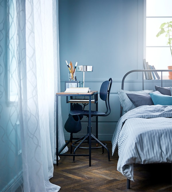A bedroom with a metal and solid wood laptop table with castors and a swivel chair in the small space between a bed and a wall.