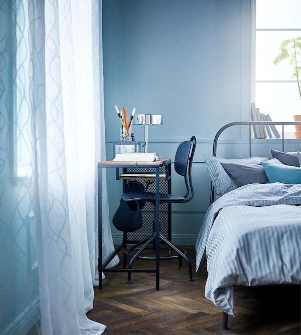 A bedroom with a metal and wood laptop table on castors and a desk chair in the small space between the bed and wall.