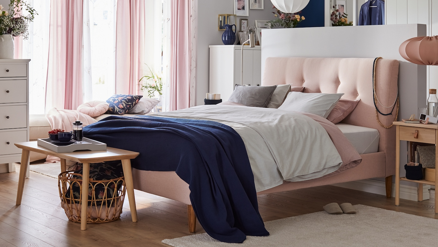 A bedroom with a pink bed with padded headboard, soft colored textiles, sheer pink curtains and wooden side tables.