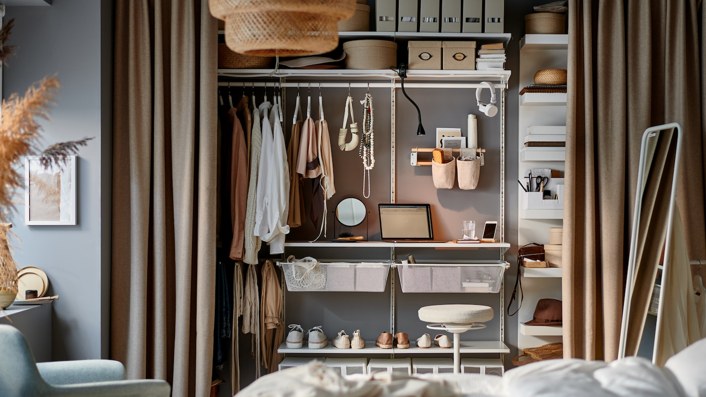 A bedroom with a small workstation occupying a few shelves of a storage system inside an open wardrobe behind curtains.