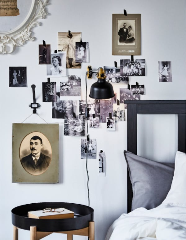 A bedroom with a vintage photo wall around the bed frame