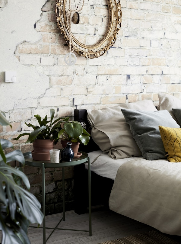 A bedroom with an exposed brick wall and plants.