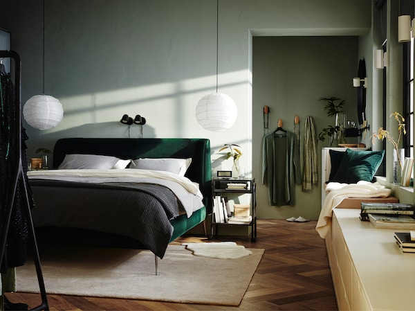 A bedroom with an upholstered bed frame in green velvet, two black wall lamps, an off-white rug and a white chest of drawers.