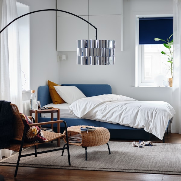 A bedroom with an upholstered bed frame with corner headboard, white quilt cover and pillowcase, a potted plant.