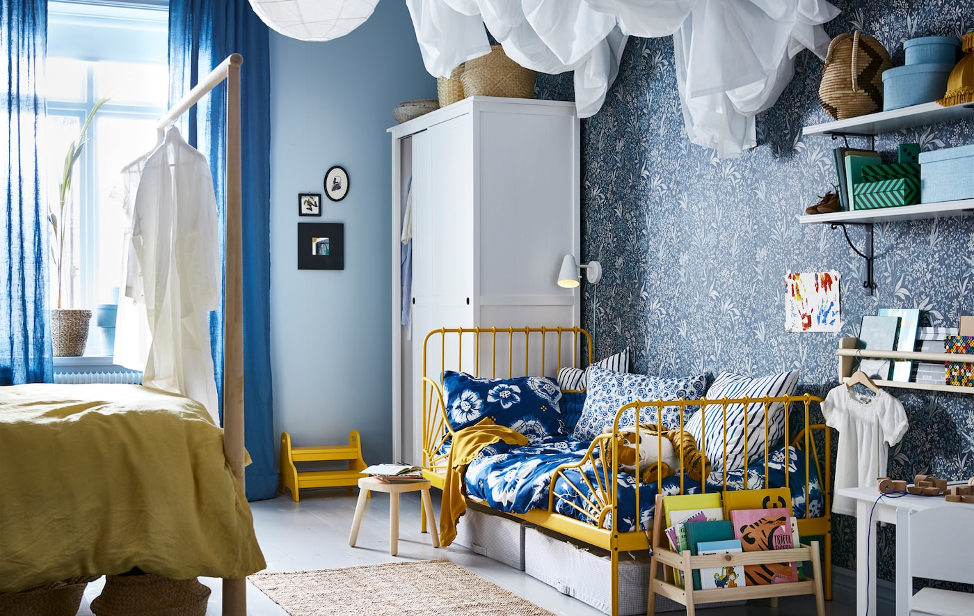 A bedroom with blue and yellow color scheme, with an adult bed on one side and child's bed on the other side.