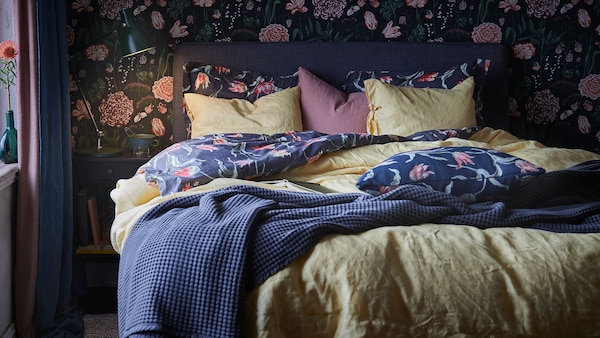 A bedroom with bold floral textiles contrasted against a chartreuse duvet cover, with flowered wallpaper in the background.