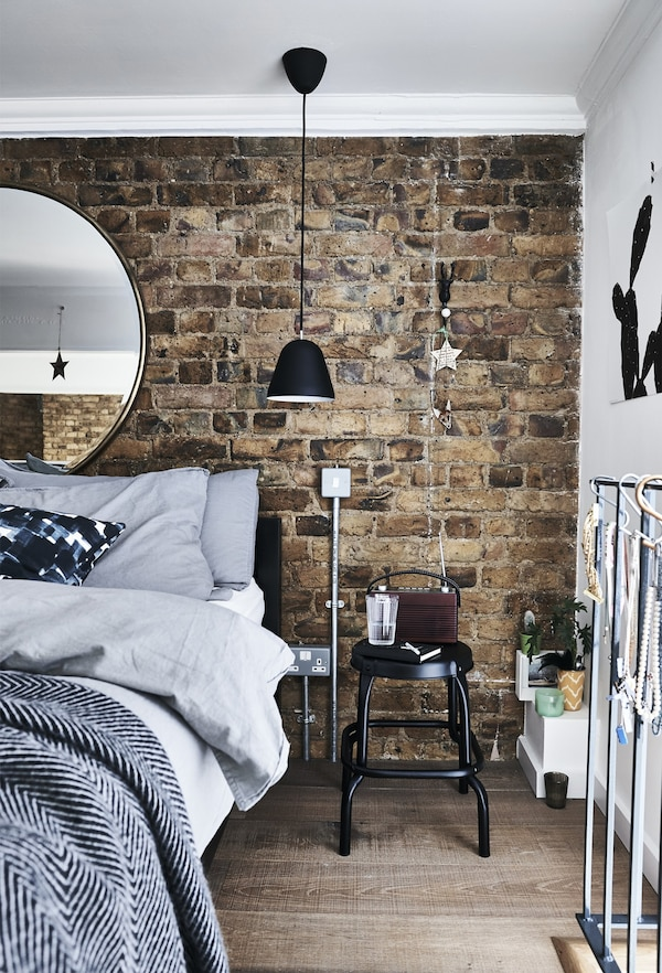 A bedroom with brick wall and grey bedding and a black stool being used as a bedside table.