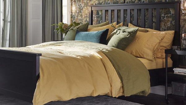 A bedroom with brown HEMNES bed and autumn colored bedding.