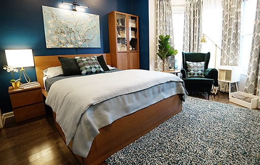 A bedroom with brown stained ashed veneer Malm bedframe, 2 drawer chest and BILLY bookcase against a dark blue accent wall.