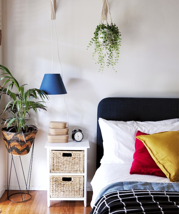 A bedroom with colourful cushions on the bed, a bedside table, and plants.