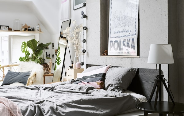 A bedroom with gray bedding, white walls and a rattan chair.