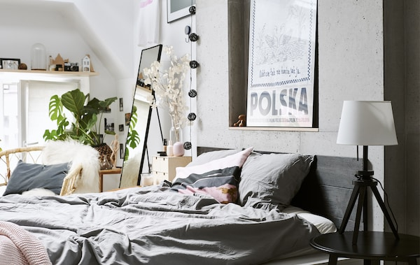 A bedroom with grey bedding, white walls and a rattan chair.