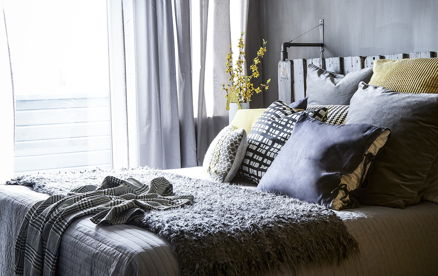 A bedroom with grey decor and yellow cushions.