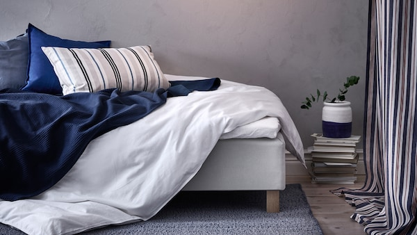 A bedroom with grey walls and a messy bed with an ÄNGSLILJA quilt cover, INDIRA bedspread in dark blue and three cushions.