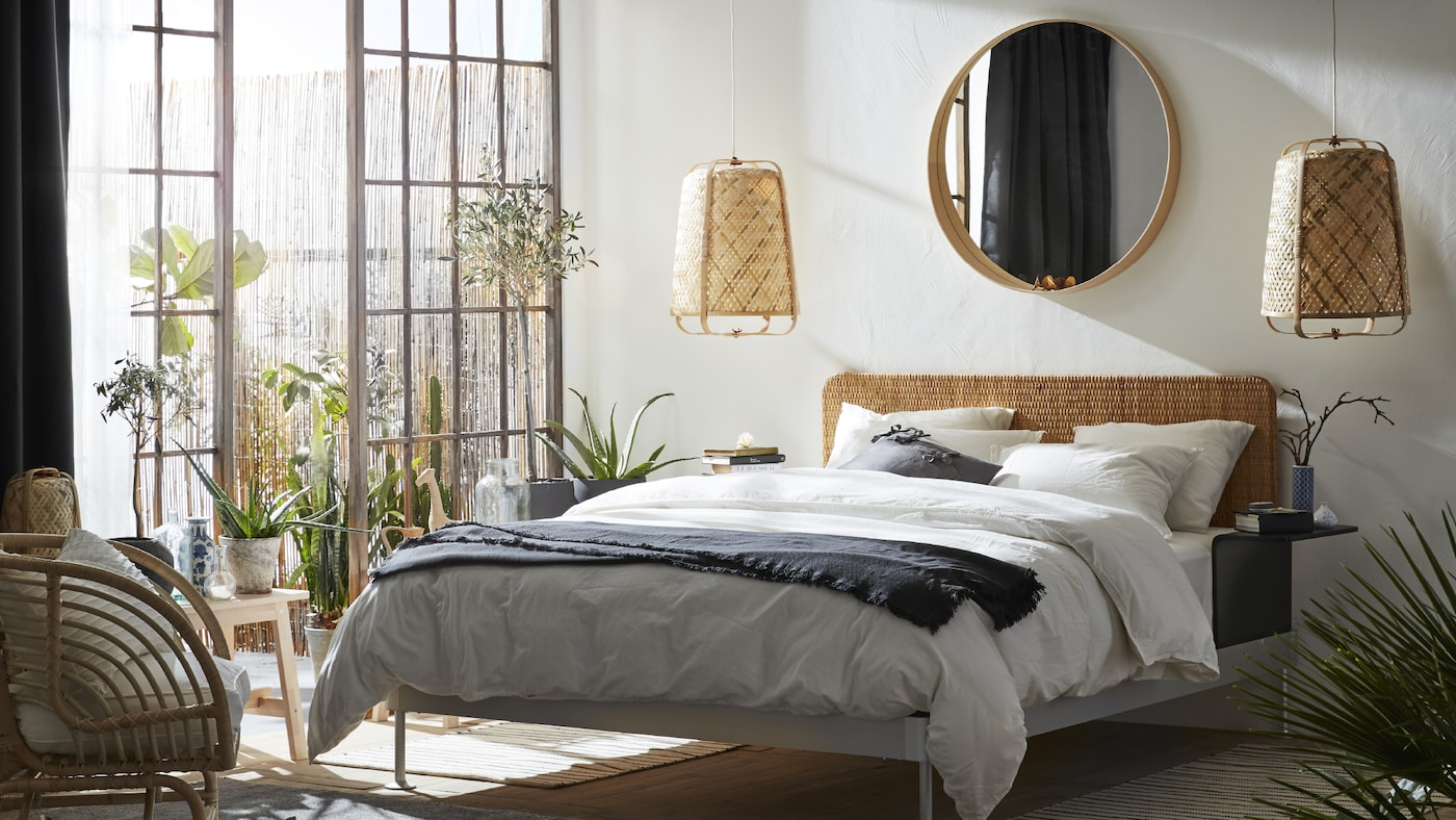 A bedroom with large French windows and a DELAKTIG bed. There is a STOCKHOLM mirror on the wall above and two pendant lamps.