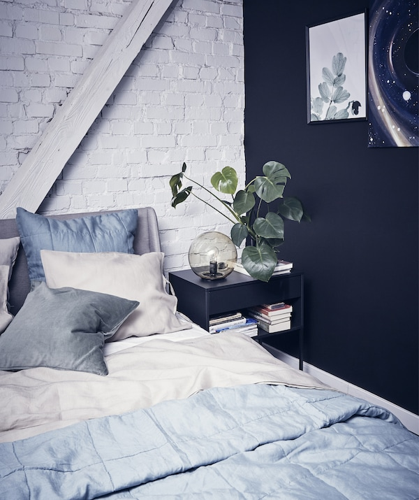 A bedroom with layered grey bedding, one black wall and one white painted brick wall.