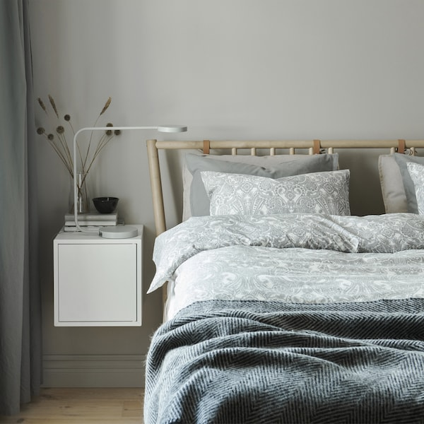 A bedroom with layers of bedding in neutral colours and a white wall-mounted bedside unit.