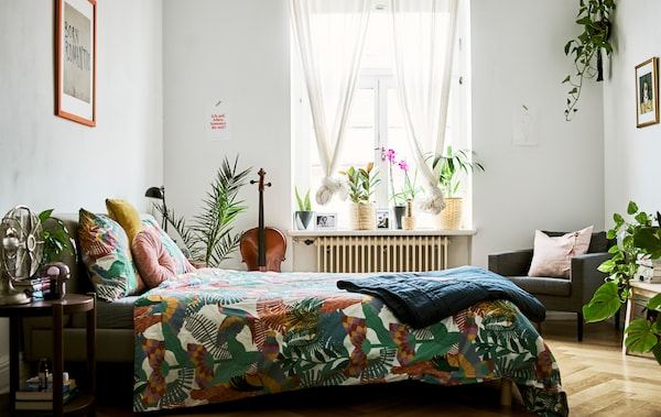 A bedroom with lots of plants, sheer curtains at the window, parquet flooring and a bed covered with a tropical-print duvet.